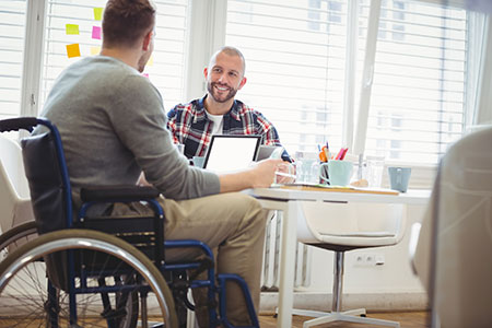 image of young man in wheelchair at work with colleague